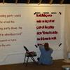 Marcia paints a stenciled quote onto the wall.