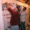 Tedrowe and Doug remove a stencil to reveal the finished quote.